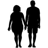 Silhouette man and woman walking hand in hand Stock Image