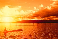 Silhouette man in the wooden boat with beautiful sunset. Mountain lake countryside view in Phayao, Thailand Royalty Free Stock Image