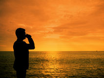 Silhouette man zipping coffee. At sunset beach Royalty Free Stock Image