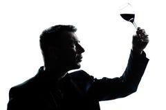 Silhouette manavsmakning som ser hans exponeringsglas Arkivfoto