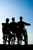 Silhouette of a mans on the bike. The silhouette three mans on the bike Stock Photo