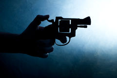 Silhouette of a mans hand with a handgun Royalty Free Stock Photos