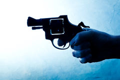 Silhouette of a mans hand with a handgun Stock Photography