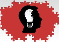 Silhouette of a mans head with a light bulb and jigsaw puzzle Stock Photography