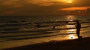 Silhouette of many people on beach and in sea in evening before sunset in holiday. Detail silhouette of many people on beach and in sea in evening before sunset Stock Photo