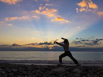 Silhouette of a martial artist training alone on the sea pier, practising his moves on sunset. Active life and. Healthcare concept royalty free stock photography