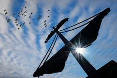 Mast of a pirate ship. Silhouette of a mast of a pirate ship with midday sun shining over blue sky background Royalty Free Stock Image