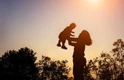 Silhouette of mather with her toddler against the sunset. And lens flare filter effect Royalty Free Stock Photography