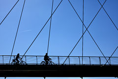 Silhouette of mature cyclists on a bridge Stock Images