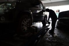 Silhouette of mechanic fixing car aligner onto car wheel Royalty Free Stock Photos