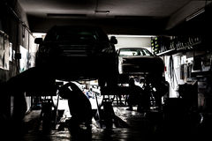 Silhouette of mechanics servicing cars at a small workshop Royalty Free Stock Photos