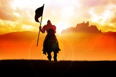 Silhouette of a medieval knight on horse carrying a flag on dram Stock Images