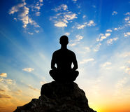 Silhouette of the meditating person. And sunshine on sky background Royalty Free Stock Photography