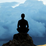 Silhouette of the meditating person. Against an approaching thunder-storm Stock Images