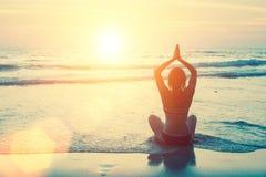 Silhouette meditating yoga woman at sunset beach Royalty Free Stock Photo
