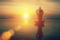 Silhouette meditation female yoga of sunset sea. Silhouette meditation female yoga on background of sunset sea Stock Photo