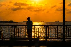 Silhouette of a men against the background of the sea at sunset Stock Images