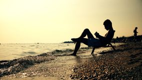 Silhouette men in chair reading book on the beach sunset. Sunrise, cinematic dof stock photo