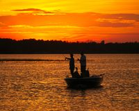 Silhouette of men fishing in a boat on lake after sunset stock images