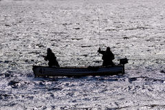 Silhouette of a men fishing from a small boat Royalty Free Stock Image