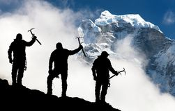 Silhouette of men with ice axe in hand and mountains Stock Photo