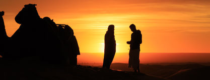 Silhouette of men standing in the desert at sunset stock images