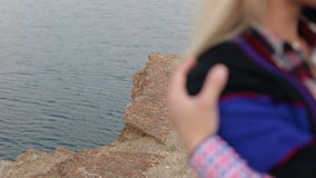 Silhouette men and women on edge of cliff by sea. Close-up silhouette of a man hugging his girlfriend`s shoulders in the background of the cliff by the sea stock footage