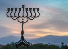 Silhouette of menorah. Traditional candelabra for Hebrew Holiday against the colorful background of cloudscape at sunrise, selective focus applied Royalty Free Stock Images