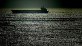 Silhouette of a merchant ship in a twilight sea Stock Photography