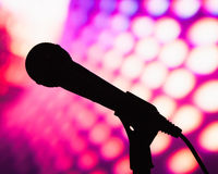 Silhouette of microphone. Against purple disco background royalty free stock photo