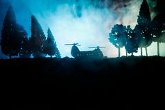 Silhouette of military helicopter ready to fly from conflict zone. Decorated night footage with helicopter starting in desert with. Foggy toned backlit Royalty Free Stock Photography