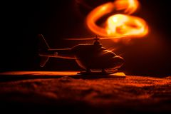 Silhouette of military helicopter ready to fly from conflict zone. Decorated night footage with helicopter starting in desert with. Foggy toned backlit stock images