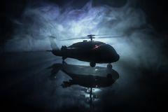 Silhouette of military helicopter ready to fly from conflict zone. Decorated night footage with helicopter starting in desert with. Foggy toned backlit royalty free stock image