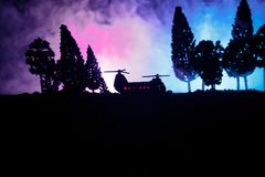 Silhouette of military helicopter ready to fly from conflict zone. Decorated night footage with helicopter starting in desert with. Foggy toned backlit Stock Photo