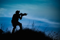 Silhouette of military soldier or officer with weapons at night. vector illustration