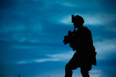 Silhouette of military soldier or officer with weapons at night. Royalty Free Stock Photography