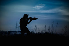 Silhouette of military soldier or officer with weapons at night. Royalty Free Stock Photos