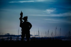 Silhouette of military soldier or officer with weapons at night. Royalty Free Stock Photo