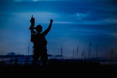 Silhouette of military soldier or officer with weapons at night. Stock Photos