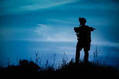 Silhouette of military soldier or officer with weapons at night. Royalty Free Stock Image