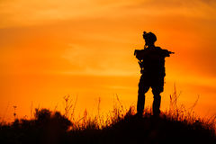 Silhouette of military soldier or officer with weapons at sunset Royalty Free Stock Photography