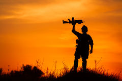 Silhouette of military soldier or officer with weapons at sunset Stock Photos
