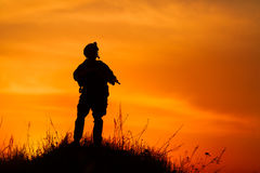 Silhouette of military soldier or officer with weapons at sunset Royalty Free Stock Photos