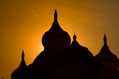 Silhouette of minaret towers. Silhouette of tips of minarets at sunset with orange background Stock Image