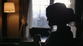 Silhouette of model woman sitting in front of the window with light leaks in slow motion
