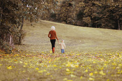 Silhouette of mom and baby in autumn day. Happy family walking Royalty Free Stock Images