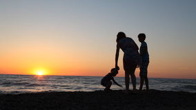 Silhouette of mom and son at sunset beach sea ocean stock footage