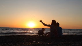 Silhouette of mom with two boys sitting on a beach with sons sea at sunset. Silhouette of mom with two boys sitting on a beach with sons stock footage