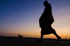 Silhouette of monk feet walking on concrete ground for people of Stock Image