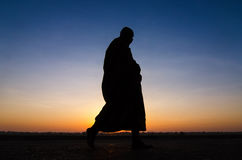 Silhouette of monk feet walking on concrete ground for people of Stock Images